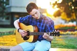ragazzo-impara-a-suonare-chitarra-acustica